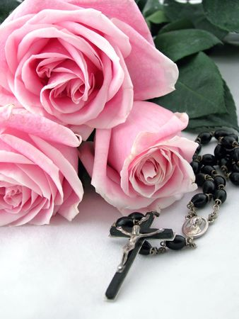 a rosary cross surrounded by pink roses