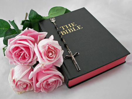 a rosary cross pink roses and bible