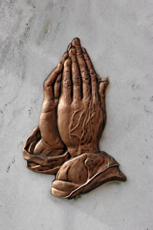 praying hands embossed on a marble plaque Stock Photo