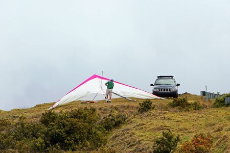 hang glider: Man Assembling Hang Glider on Mountain Top