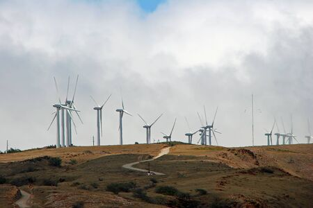 windfarm: Wind Mills Turbines Mountaintop against Cloudy Sky