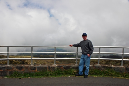 guardrail: Middle-age Man Standing by Foggy Mountaintop Guardrail