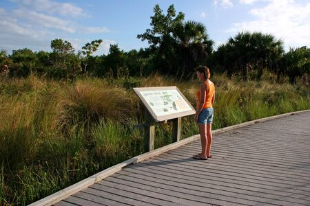 sanctuary: Woman Reading Sign Ding Darling Sanibel Florida ; Bailey Tract Stock Photo