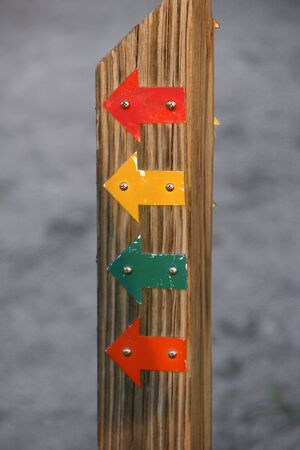 symbolization: Colorful Directional Arrows on a Wooden Pole