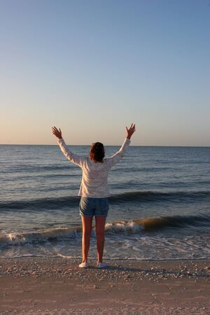 Woman on Beach With Arms Upraised Sunrise Sanibel Florida photo