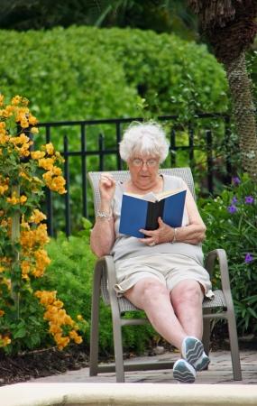lounge: Senior Woman Reading Book Outside Lounge Chair