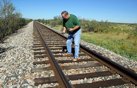 cross ties: Man on Railroad Tracks Searching for Rusted Cut Spikes Stock Photo