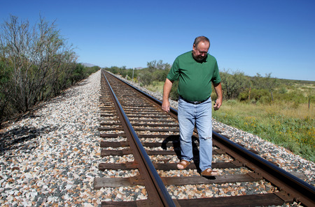 wood railroad: Man on Railroad Tracks Searching for Rusted Cut Spikes Stock Photo