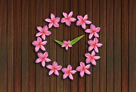 pink frangipani clock on wood background photo