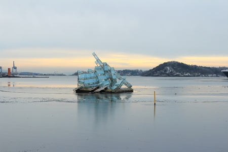 Oslo, Norway - December 30, 2018: She Lies, sculpture floating in the ocean water next to the Opera House of Oslo, Norway.