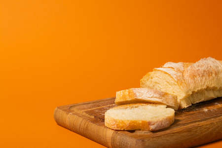 Sliced bread baguette on a wooden cutting board on a terracote color background. Close-up high quality photo.