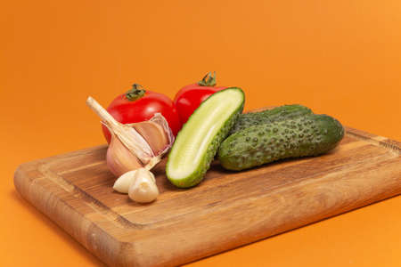 Sliced cucumber, tomatoes and garlic on wooden cutting board. Tomatoes with green ponytails. Healthy food. Copy space. High quality close-up photo