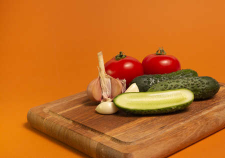 Sliced cucumber, tomatoes and garlic on wooden cutting board. Tomatoes with green ponytails. Healthy food. Copy space. High quality close-up photo.