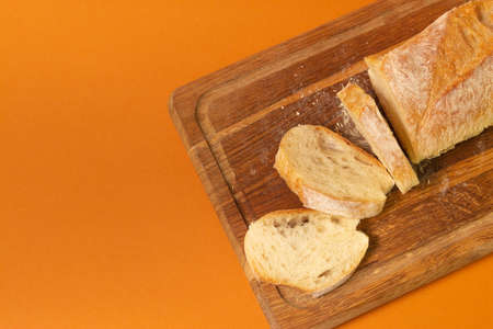 Sliced bread baguette on a wooden cutting board on a terracote color background. Close-up high quality photo