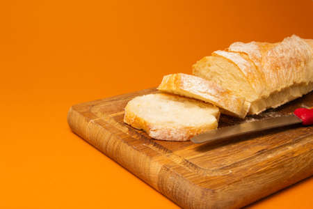 Sliced bread baguette on a wooden cutting board with knife on a terracote color background. Copy space. Close-up high quality photo.