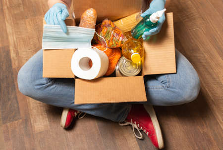 A person sitting on the floor and holding donation box with food, toilet paper and sanitizer. Food delivery service for those who need. High quality photo.