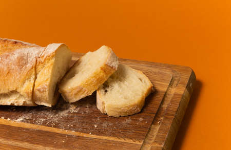 Sliced bread baguette on a wooden cutting board on a terracote color background. Close up high quality photo.