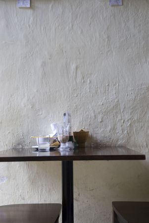 A table and chair set against a wall in a cafe, Melaka, Malaysia photo