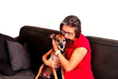 greying: A Woman cuddling with dog on a grey sofa