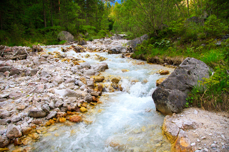 Mountain stream flowing between rocks Stock Photo