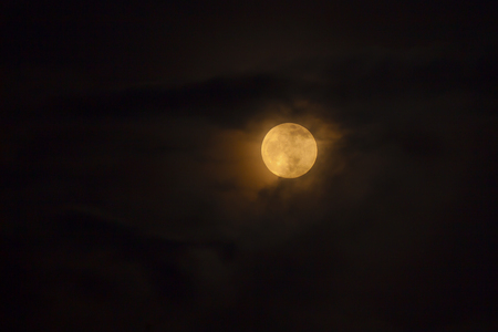 timeless: Full golden moon behind the clouds