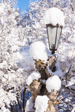 Satyr statue lamp covered in snow in Warsaw Lazienki park, after heavy snow fall, lazienki
