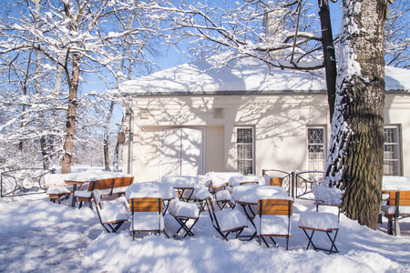 Tables and chairs near building entrance covered with heavy layer of snow, Warsaw, Poland