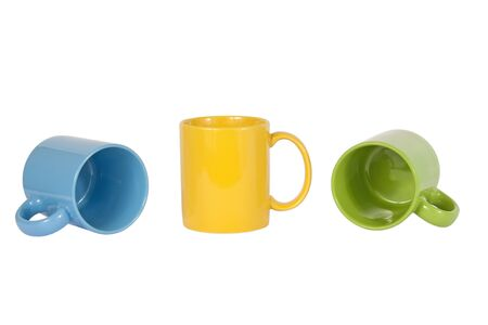 Three cups, one blue, one yellow and one green, isolated on white background photo