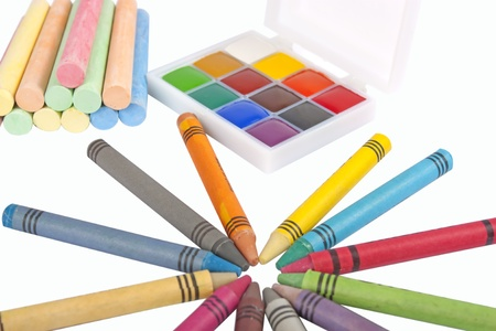 Colored wax pencils, chalk and a watercolor isolated on a on white background photo