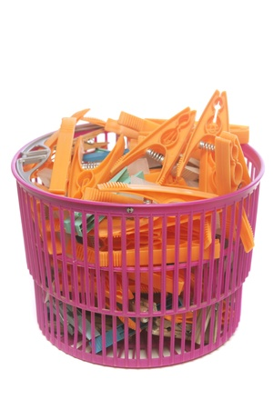 Colored clothes pegs in plastic basket isolated over white background photo