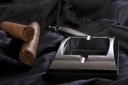 Close up of  metallic ashtray, lighter and cuban cigar on black silk background Stock Photo