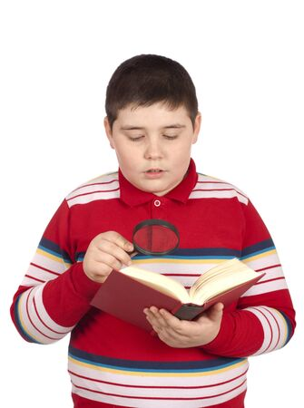 Boy reading a book with magnifier, isolated over white background photo