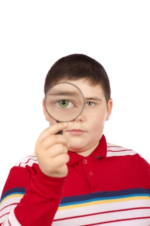 Young boy looking through a magnifying glass isolated over white background photo