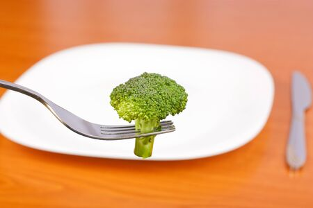 Broccoli in fork and one plate and knife in background photo