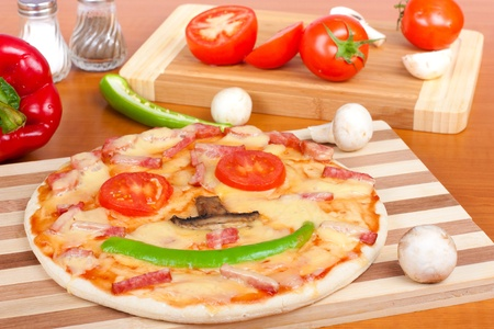 Pizza smiling on cutting board and fresh vegetables photo