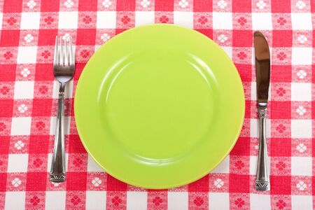 Knife, green plate and fork on red checked tablecloth  photo