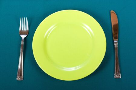 Knife, green plate and fork on blue tablecloth photo