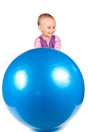 Baby girl with a blue fitness ball isolated on white background