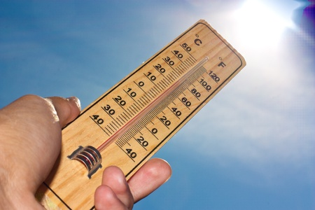 Wooden thermometer on a blue sky against the sun