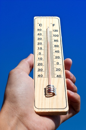 Wooden thermometer against on a blue sky photo