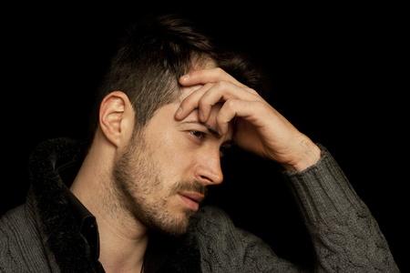 Sad man isolated on a black background