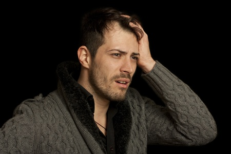 Man stressed with his hand on his head as if he had a headache - isolated over a black background Stock Photo - 11396594