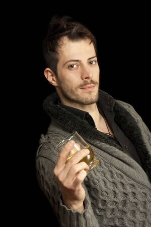 Young man holding a glass isolated over black background Stock Photo - 11396593