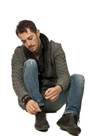 흰색 배경 위에 고립 된 그의 신발 끈으로 묶는 젊은 남자, 스톡 콘텐츠