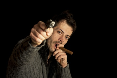 Mafia man smoking cigar with handgun, isolated over black background photo