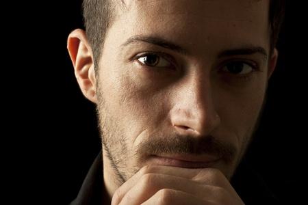 hombre pensando: Joven pensando en una soluci�n, aislado en negro
