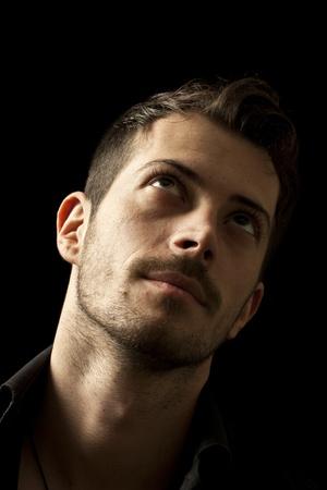 Young handsome man looking up, isoliert auf schwarzem Hintergrund Standard-Bild - 11641157