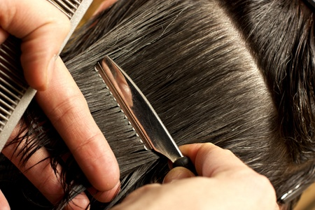 Woman going to cut her hair with scissors