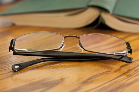 Book with reading glasses on wood photo