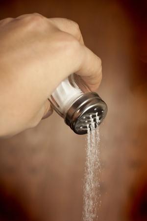 Hand adding salt using a salt shaker on a wood background Stock Photo